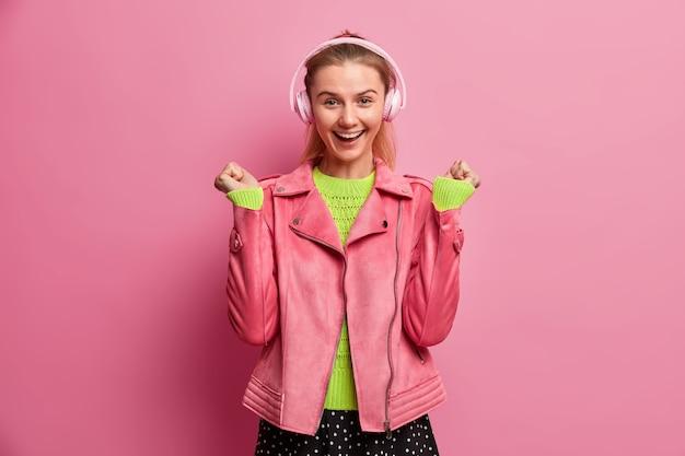 Disparo aislado de feliz adolescente escucha música a través de auriculares inalámbricos estéreo levanta los puños cerrados y sonríe ampliamente