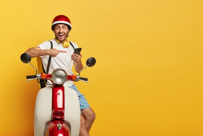 Disparo aislado de feliz guapo conductor masculino en scooter con casco rojo