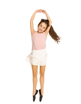 Disparo aislado de feliz niña sonriente acostada en el suelo y bailando ballet