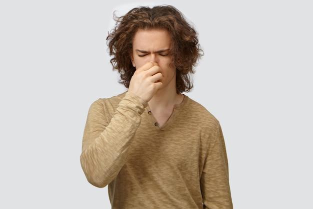 Disparo aislado de un guapo joven europeo frustrado con mangas largas cerrando los ojos y pellizcando la nariz, sintiéndose disgustado por el mal olor o el hedor de axilas sudorosas o calcetines sucios