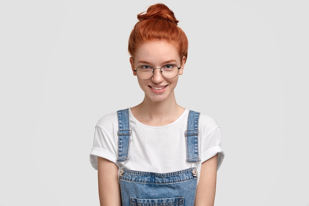 Disparo aislado de hermosa adolescente pecosa en overoles de mezclilla, gafas ópticas redondas, sonríe positivamente