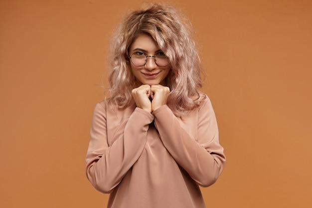 Disparo aislado de hermosa joven encantadora con cabello rosado y linda sonrisa sintiéndose tímida