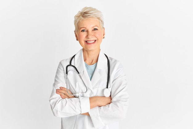 Disparo aislado de médico senior maduro exitoso feliz vistiendo uniforme médico y estetoscopio con expresión facial alegre, sonriendo ampliamente, manteniendo los brazos cruzados sobre el pecho