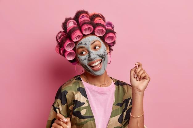 Disparo aislado de mujer positiva mira a un lado sonríe ampliamente levanta el brazo aplica rulos máscara de belleza vestida con bata doméstica se prepara para ocasiones especiales quiere lucir hermosas modelos en interiores