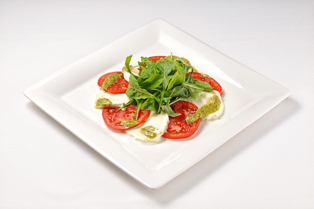 Disparo aislado de un plato blanco con ensalada caprese: perfecto para un blog de comida o uso de menú