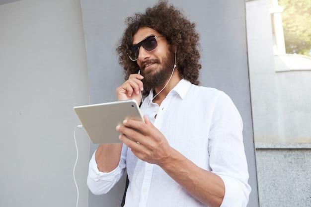 Disparo al aire libre con un apuesto joven hombre rizado sosteniendo la tableta en la mano y teniendo una conversación en línea con auriculares, gafas de sol y camisa blanca
