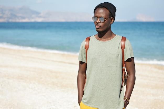 Disparo al aire libre de un atractivo macho africano serio con gafas redondas y sombrero para pasar las vacaciones junto al mar