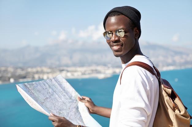 Disparo al aire libre de un atractivo turista de piel oscura que estudia el mapa de papel en sus manos, con gafas y sombrero, de pie en la plataforma de turismo, contemplando el increíble mar azul debajo