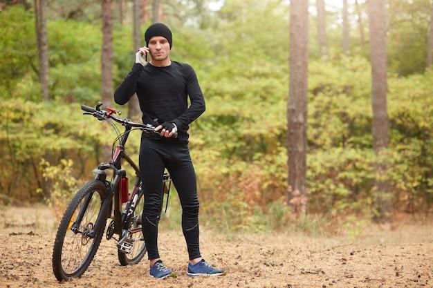Disparo al aire libre del hombre vestido con un traje negro y zapatillas de deporte, de pie cerca de su bicicleta de montaña y habla por teléfono con un hermoso bosque en backgraund, pasando tiempo en forma activa. concepto de estilo de vida saludable.
