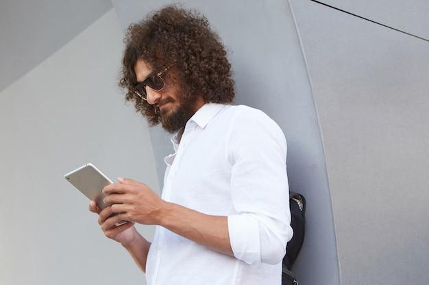 Disparo al aire libre de un joven atractivo con barba, con gafas y camisa blanca, sosteniendo la tableta en las manos y mirando la pantalla, posando sobre una pared gris