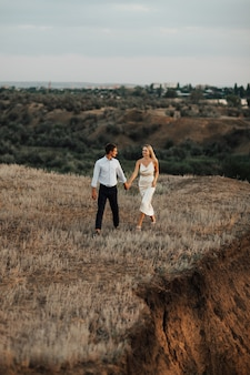 Disparo al aire libre de una joven pareja caminando por la colina y tomados de la mano.
