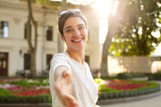 Disparo al aire libre de positivo joven encantadora mujer de cabello oscuro con peinado casual mirando alegremente con la palma levantada y sonriendo agradablemente