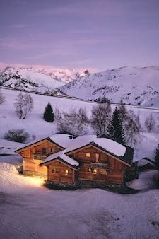 Disparo de alto ángulo de una acogedora cabaña en la estación de esquí de alpe d huez en los alpes franceses en francia