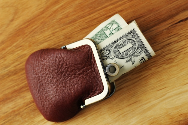 Disparo de alto ángulo de algo de dinero en efectivo en un monedero de cuero sobre una superficie de madera