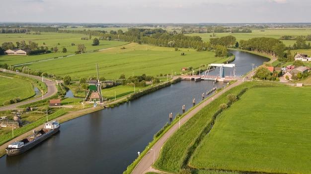 Disparo de alto ángulo del canal merwede rodeado por campos de hierba capturados en nehterlands