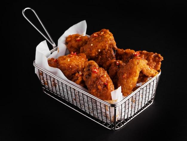 Disparo de alto ángulo de una canasta de delicioso pollo frito sobre una superficie negra