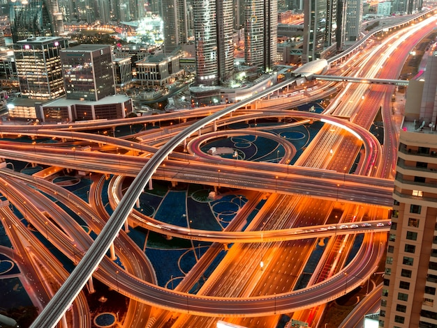 Disparo de alto ángulo de una carretera iluminada con intersecciones de varios niveles en una megapolis en la noche