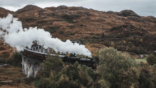 Disparo de alto ángulo del famoso histórico tren de vapor en el viaducto de glenfinnan, escocia