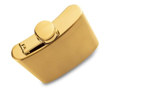 Disparo de alto ángulo de un frasco de licor dorado sobre una superficie blanca