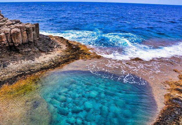 Disparo de alto ángulo de un hermoso mar rodeado de formaciones rocosas en las islas canarias, españa