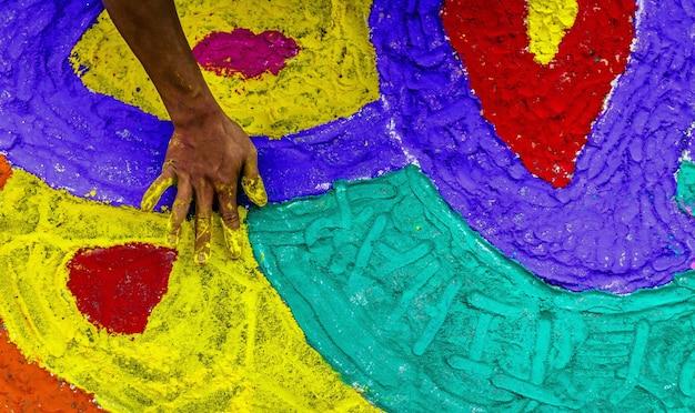 Disparo de alto ángulo de la mano de una persona pintando el suelo con tiza en nepal