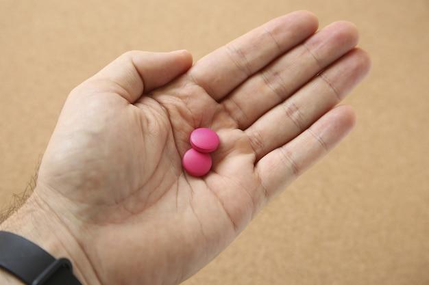 Disparo de alto ángulo de la mano de un ser humano con dos pastillas de color rosa sobre rosa