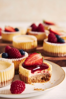 Disparo de alto ángulo de pastelitos de queso con mermelada de frutas y frutas en una placa de madera