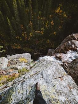 Disparo de alto ángulo de una persona de pie sobre una roca en la cima de una cascada en noruega