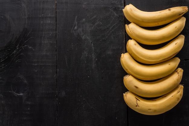 Disparo de alto ángulo de plátanos con un espacio de copia sobre un fondo negro