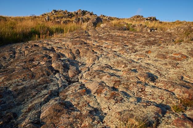 Disparo de alto ángulo de una superficie rocosa con hermosos paisajes de puesta de sol en un cielo azul claro