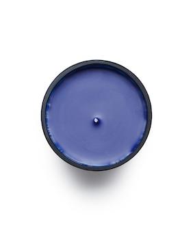 Disparo de alto ángulo de una vela perfumada púrpura bajo las luces aislado sobre un fondo blanco.