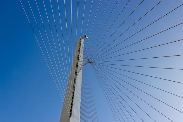 Disparo de ángulo bajo de cables de acero con un cielo azul claro
