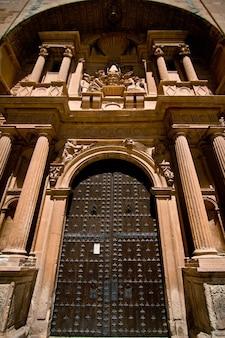Disparo de ángulo bajo vertical de la puerta de acero en la entrada de un magnífico edificio histórico