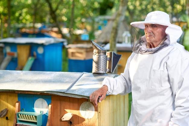 Disparo de un apicultor en traje de apicultura de pie cerca de la fila de colmenas en su copyspace colmenar.