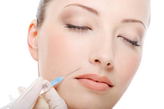 Disparo de botox en la mejilla femenina - primer plano del rostro femenino