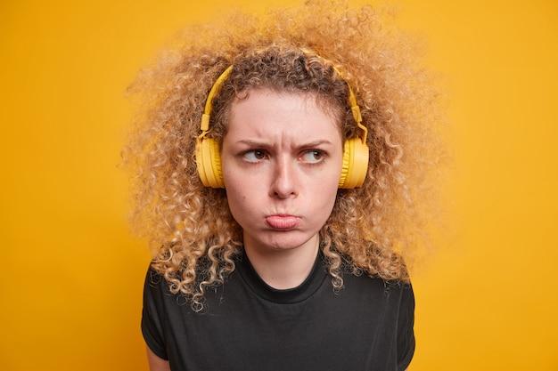 Disparo en la cabeza de una adolescente de pelo rizado disgustada tiene mal humor expresión de la cara enfurruñada usa auriculares estéreo inalámbricos escucha música vestida con una camiseta negra casual aislada sobre una pared amarilla