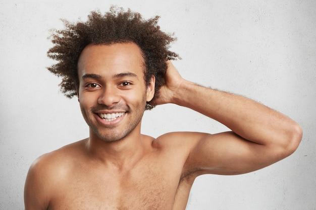 Disparo en la cabeza del atractivo chico afroamericano con peinado tupido, desnudo, contento de tener deporte