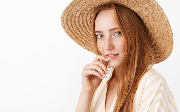 Disparo en la cabeza de una elegante y encantadora y coqueta mujer pelirroja con pecas en un sombrero de paja y una blusa amarilla de moda mordiendo el dedo y mirando con deseo y mirada sensual posando femenina