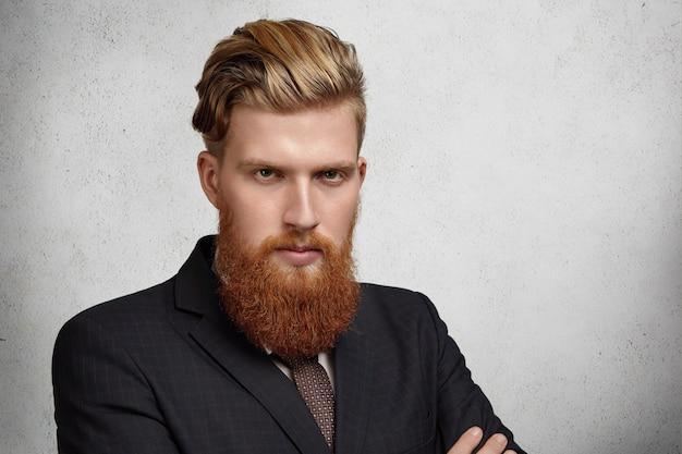Disparo en la cabeza de un joven trabajador corporativo atractivo con un corte de pelo moderno y una larga barba roja, vestido con un elegante traje y una expresión facial enfocada y concentrada, listo para una reunión de negocios seria