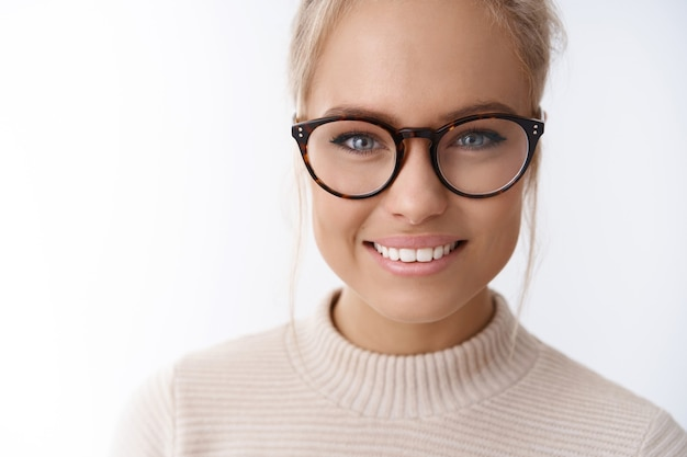 Disparo en la cabeza de la mujer elegante atractiva soñadora esperanzada en gafas de moda con el pelo peinado sonriendo mirando amistoso y divertido en la cámara divirtiéndose expresando emociones positivas contra el fondo blanco