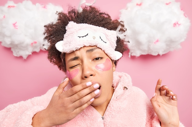 Disparo en la cabeza de una mujer joven de pelo rizado que cubre la boca con la mano tiene expresión de sueño se despierta temprano en la mañana se somete a tratamientos de belleza después de despertar usa ropa de dormir cómoda
