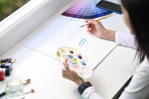 Disparo en la cabeza de la mujer sosteniendo la paleta de colores y el cuadro de pintura de pincel en su taller.
