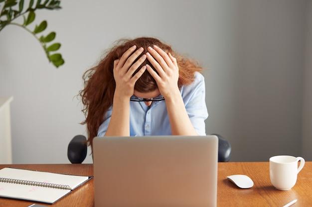 Disparo en la cabeza del trabajador de oficina femenino pelirrojo agotado en camisa azul y gafas