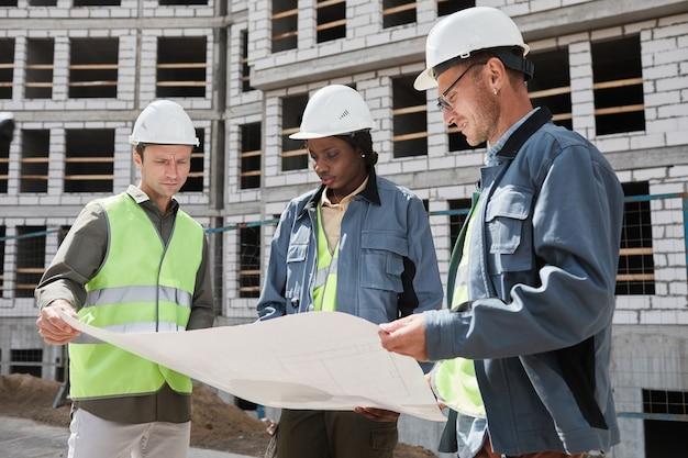 Disparo de cintura para arriba de diverso grupo de ingenieros discutiendo planos de planta en el sitio de construcción