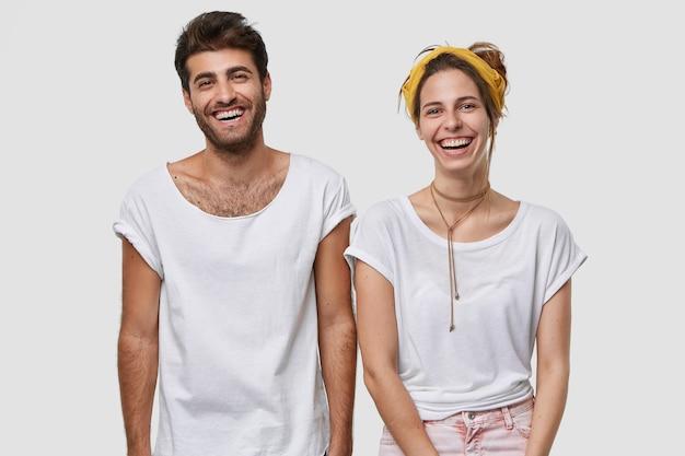 Disparo de cintura para arriba de felices compañeros femeninos y masculinos vestidos con camiseta blanca de maqueta, sonríen ampliamente, están en alto espíritu, están de pie cerca uno del otro, aislado sobre la pared