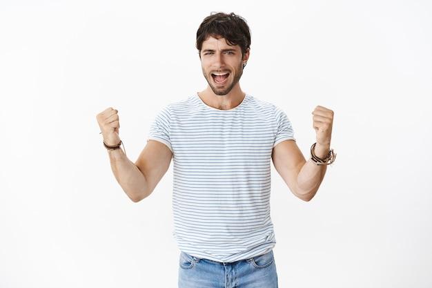 Disparo de cintura para arriba de un hombre apuesto, alegre y solidario, con ojos azules y una camiseta rayada erizada que grita y levanta los puños cerrados mientras triunfa, es fanático y un equipo solidario sobre la pared blanca