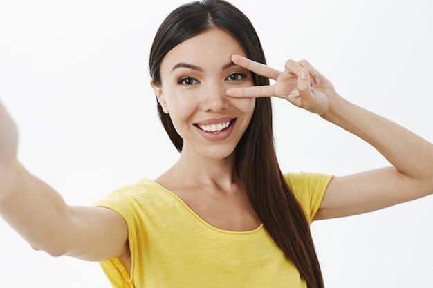 Disparo de cintura para arriba de linda mujer asiática alegre de aspecto amistoso que muestra la paz o el signo de la discoteca sobre el ojo sonriendo ampliamente