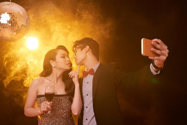 Disparo a la cintura de una pareja en ropa elegante dando un beso para una selfie en una fiesta
