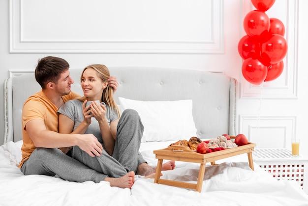 Disparo completo feliz pareja en la cama con desayuno