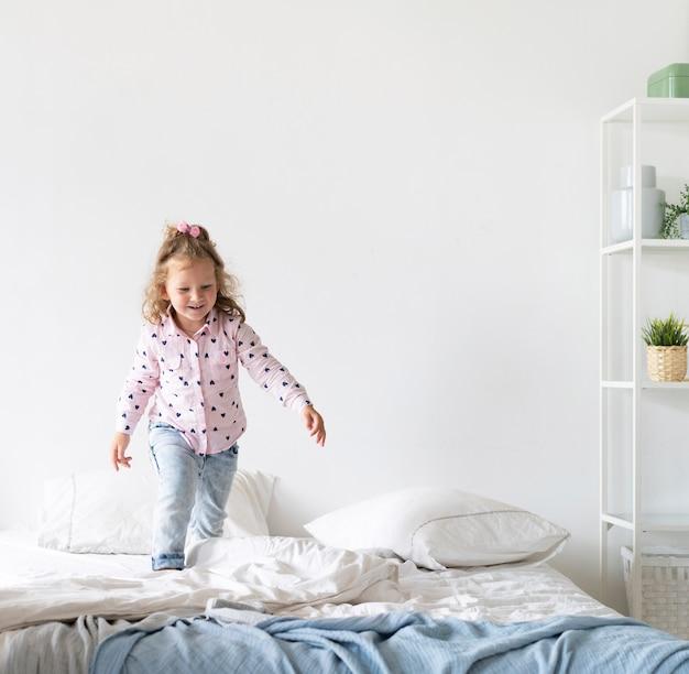 Disparo completo niña feliz caminando en la cama